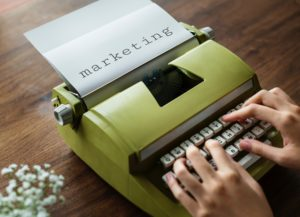 """A green typewriter with paper in it that says """"marketing."""" Marketing is very important for video production."""