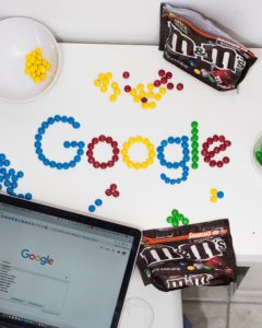 The word Google spelled out in M&Ms and Google homepage displayed on a laptop screen.