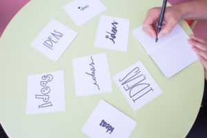 """Multiple notecards with the word """"IDEAS"""" in different fonts to signify brainstorming, which is very important for video production."""